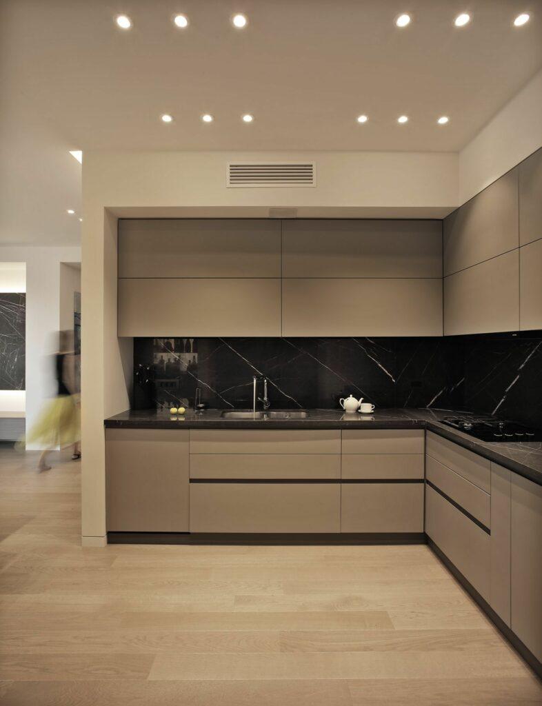 Bézs L alakú konyha fekete hátfallal