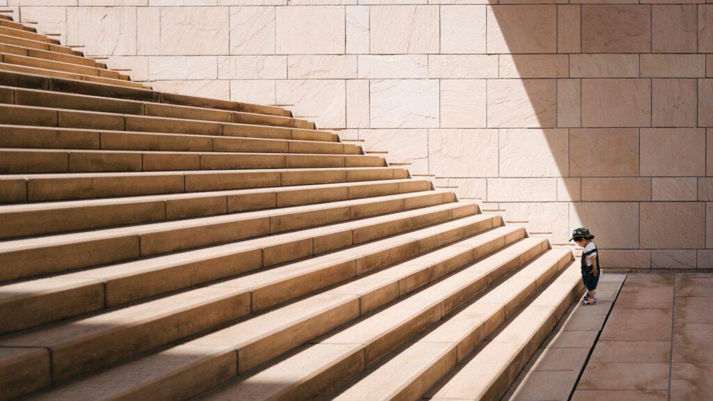 Gyerek áll a lépcső előtt